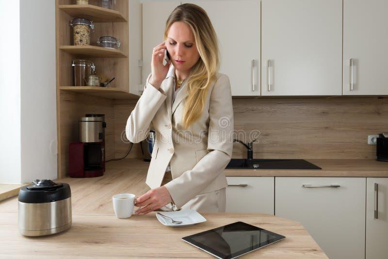 Modern affärskvinna med smartphonen och kaffe i köket arkivbild