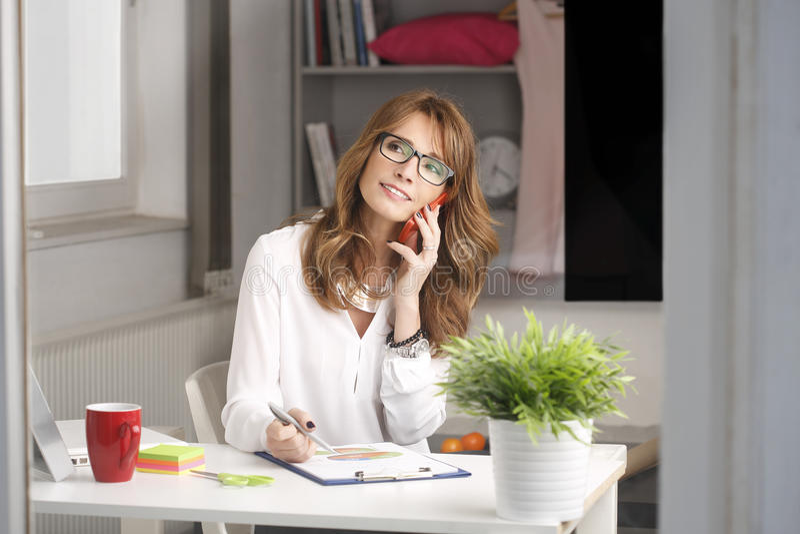 Modern affärskvinna som hemma arbetar arkivbilder