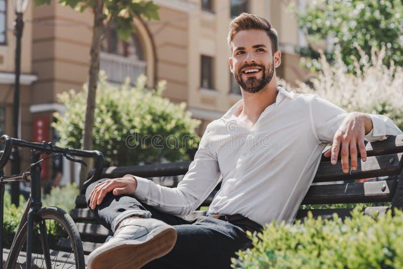 Modern affärsman Den unga le mannen som sitter på en bänk i, parkerar med en cykel bredvid honom Vila och koppla av begreppet royaltyfria bilder