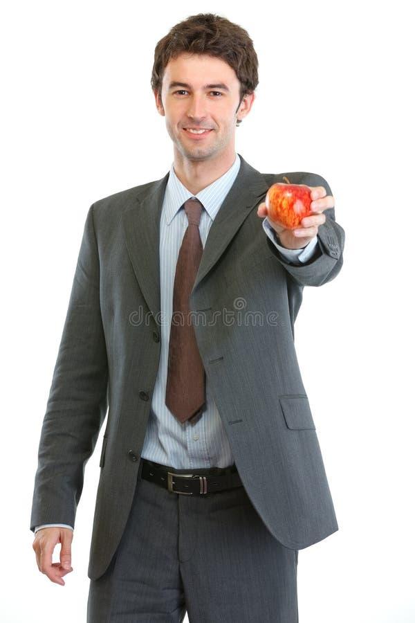 Modern affärsman som ger äpplet royaltyfri fotografi