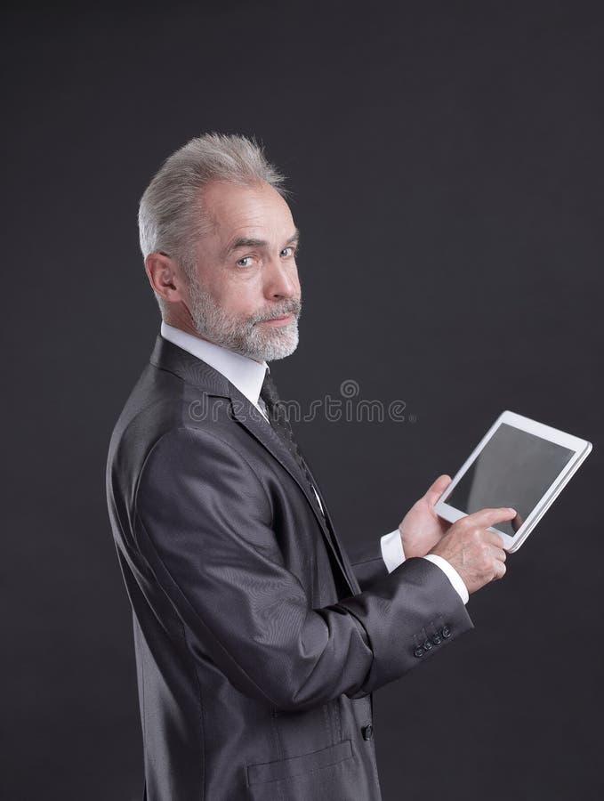 Modern affärsmanUsing Digital minnestavla Isolerat på svart bakgrund arkivfoton