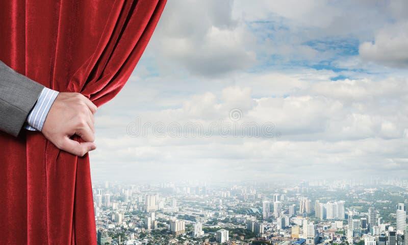 Modern aff?rscityscape bak gardinen ?ppnade vid aff?rsmanhanden arkivbilder