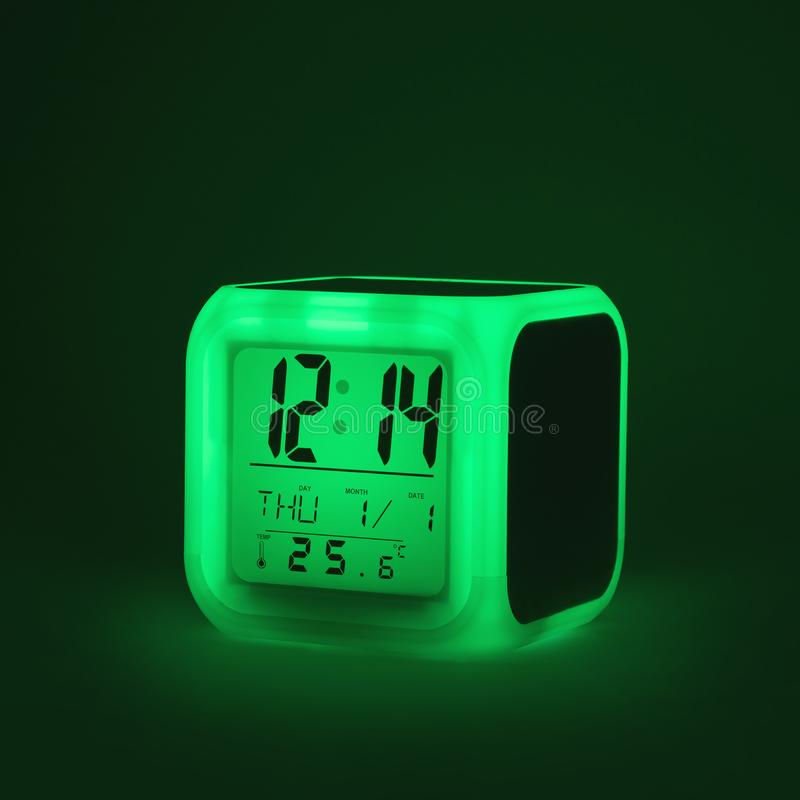 Modern alarm clock glowing light on dark backdrops and copyspace. LED light or digital display stock images