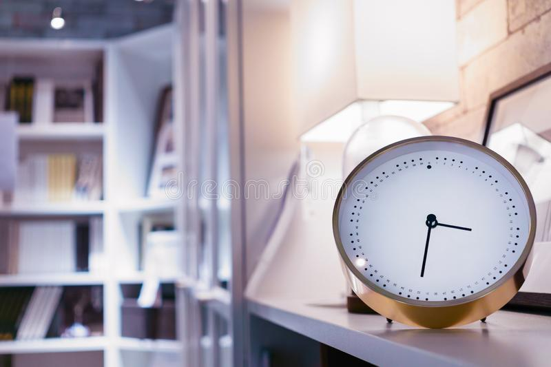 Modern alarm clock in home library and living room with blurred bookshelf background at night time stock photography