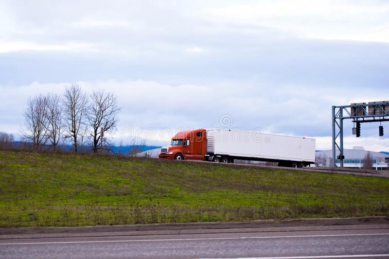 Modern big rig orange semi truck with long container trailer driving on the road stock image