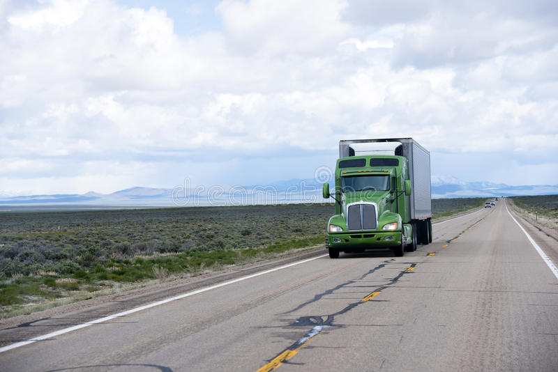Modern American semi truck and reefer trailer on Nevada road. Stylish professional powerful green big rig semi truck with a trailer and refrigeration unit stock image