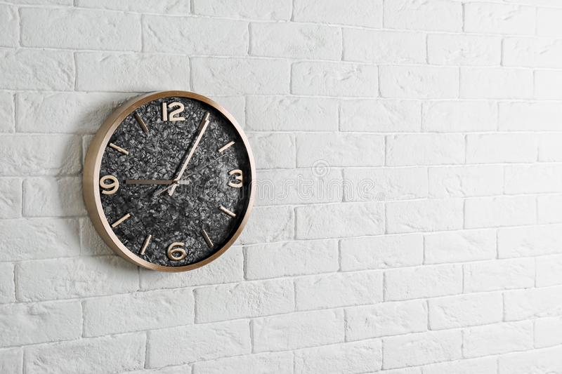 Modern analog clock hanging on white wall, space for text stock images