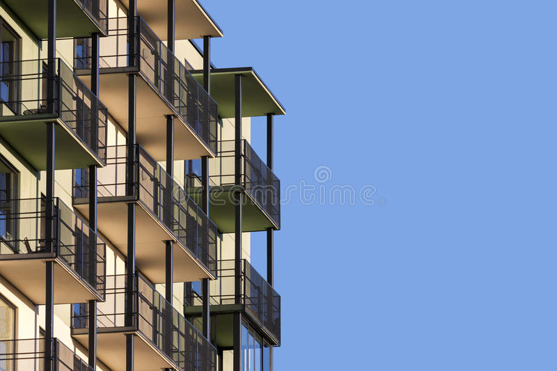Modern apartment building with balconies. Against blue sky to ad text stock image