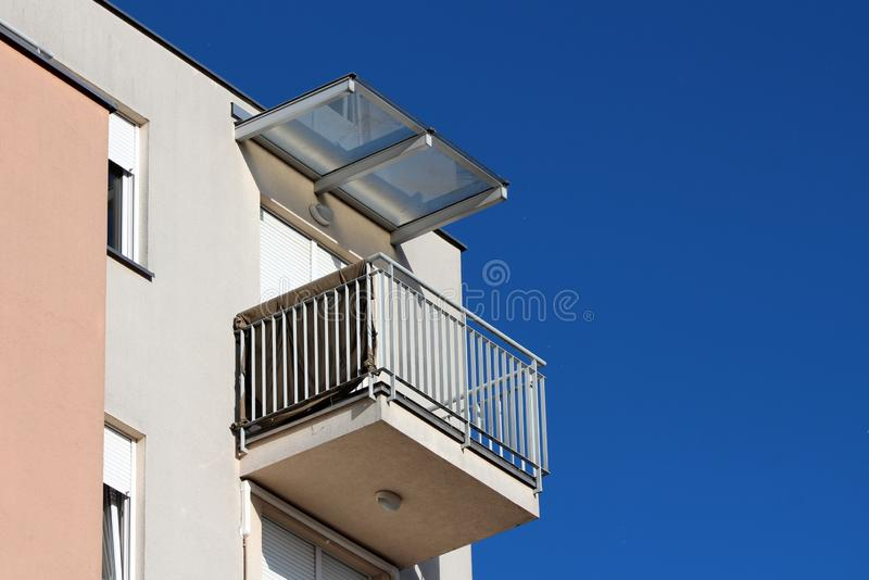 Modern apartment building corner balcony surrounded with grey metal safety fence and closed window blinds covered with transparent stock photo