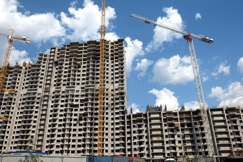 Modern apartment buildings construction in process. New high-rise modern apartment buildings construction in process ob bright sunny day front view horizontal stock photography