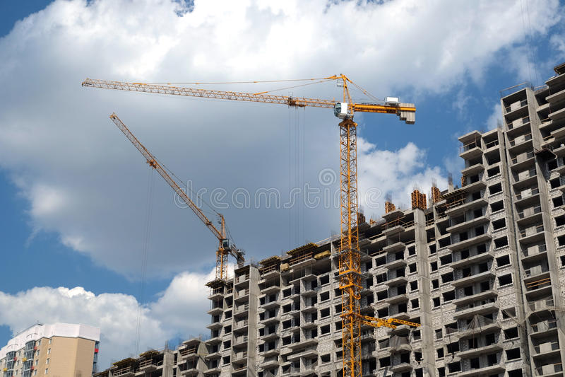 Modern apartment buildings construction in process. New high-rise modern apartment buildings construction in process ob bright sunny day front view horizontal stock images