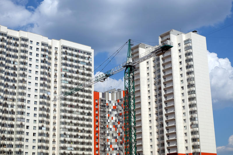 Modern apartment buildings construction in process. New high-rise modern apartment buildings construction in process ob bright sunny day front view horizontal royalty free stock photos