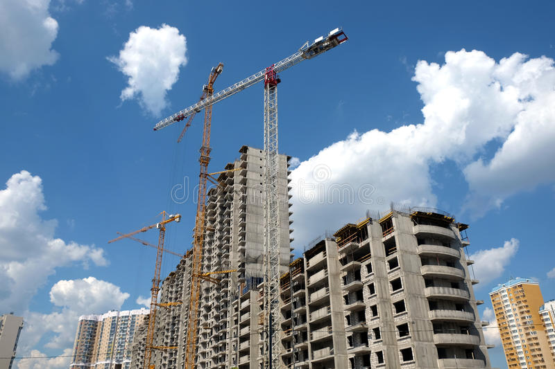 Modern apartment buildings construction in process. New high-rise modern apartment buildings construction in process ob bright sunny day side view horizontal royalty free stock images