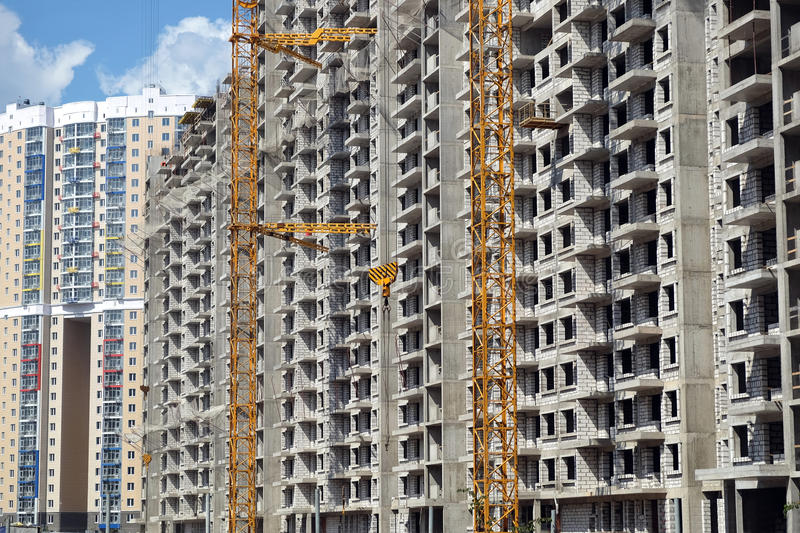 Modern apartment buildings construction in process. New high-rise modern apartment buildings construction in process ob bright sunny day side view horizontal royalty free stock photo