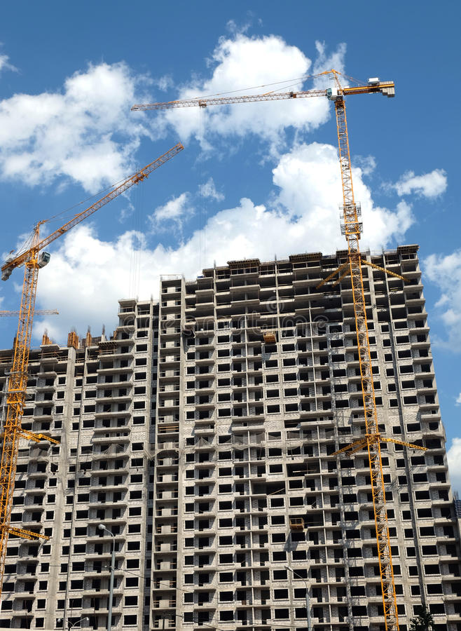 Modern apartment buildings construction in process. New high-rise modern apartment buildings construction in process ob bright sunny day side view vertical royalty free stock photography