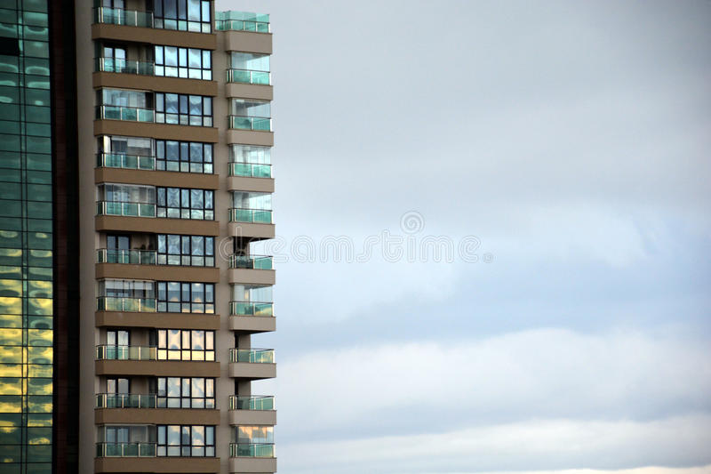 Modern apartment house against cloudy skies. With glass windows and balconies royalty free stock photo