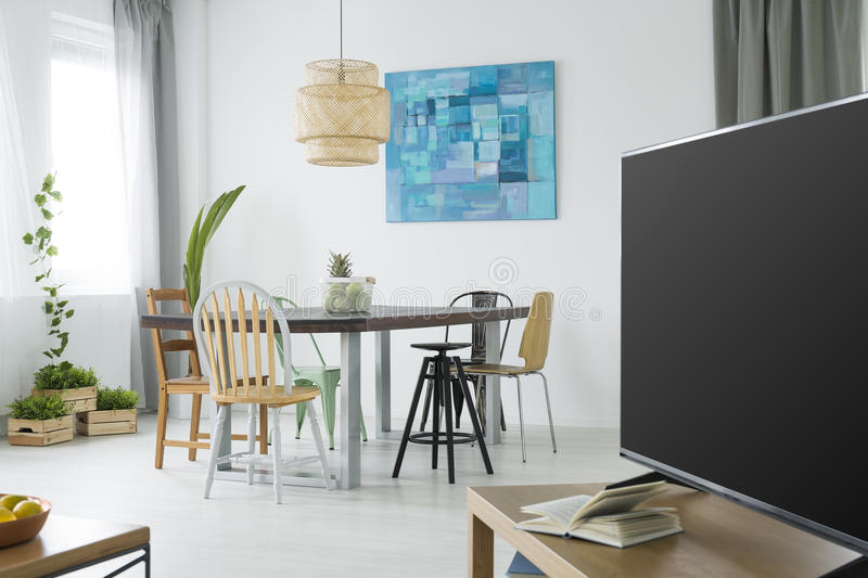 Modern apartment with tv. Dining table and chairs royalty free stock image