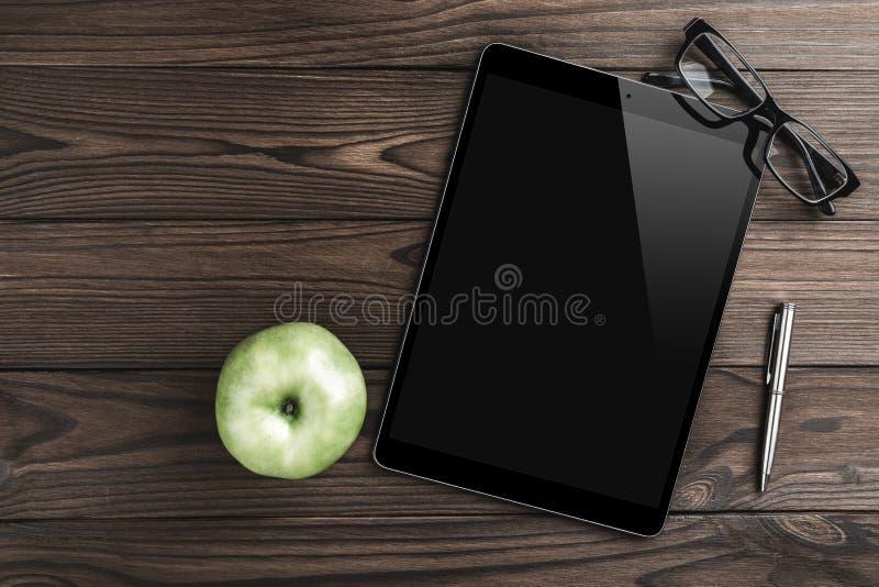 Modern arbetsplats med den digitalt minnestavladatoren, silverpennan, äpplet och glasögon Utrymme för bästa sikt och kopierings fotografering för bildbyråer