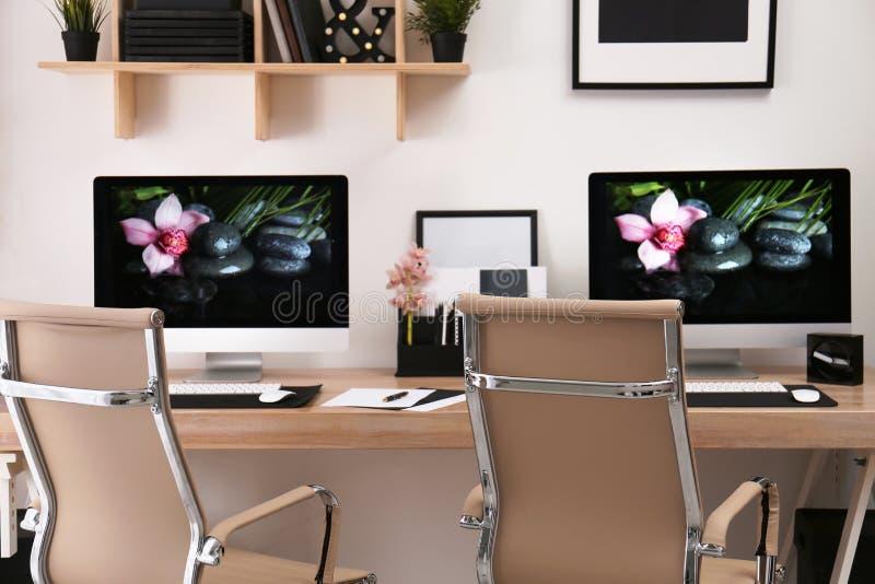 Modern arbetsplats med det stora skrivbordet och datorer i rum fotografering för bildbyråer