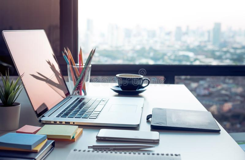 Modern arbetstabell med datorbärbara datorn och cityscapessikt från fönster affärsidéidéer arkivfoto