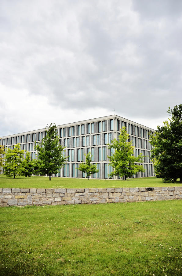 Modern architecture building full of windows during a storm. Point of view of a modern building with windows from the garden which surrounds it, during a storm royalty free stock photo