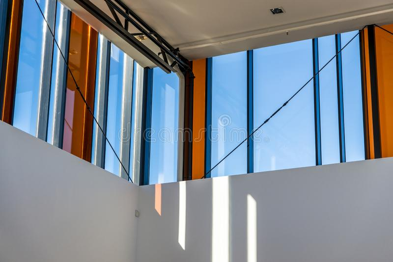 Modern architecture details in sunlight with windows and blue sky. Modern architecture detail from inside building, with windows letting in sunlight through royalty free stock photo