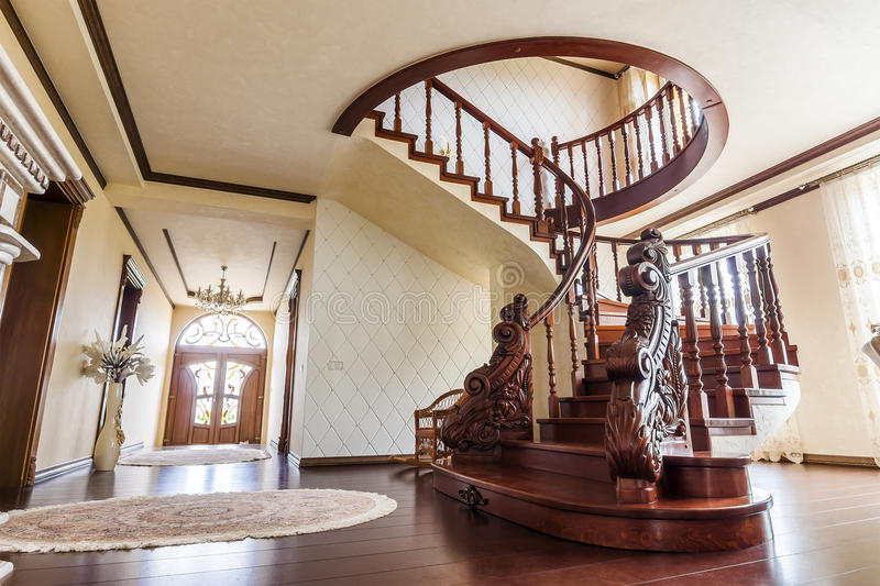 Modern architecture interior with classic elegant luxury hallway. With curved glossy wooden staps stairs in modern storey house royalty free stock photo