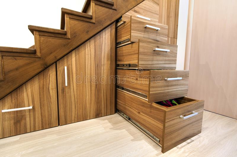 Modern architecture interior with luxury hallway with glossy wo. Oden stairs in modern storey house. Custom built pullout cabinets on glides in slots under stock images