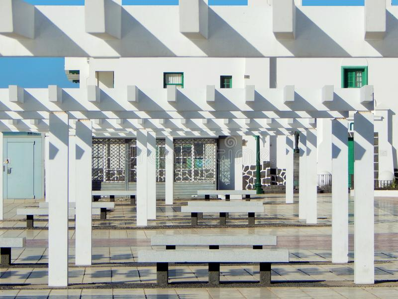 Modern architecture with pergola in front. Blue sky in the back and light and shadow caused by the sunlight royalty free stock photo