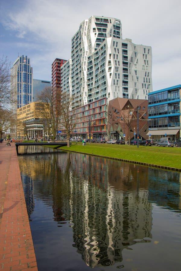 Modern architecure av stadsmitten av Rotterdam med reflexioner på kanalen, bron och grönområde i förgrund arkivfoton