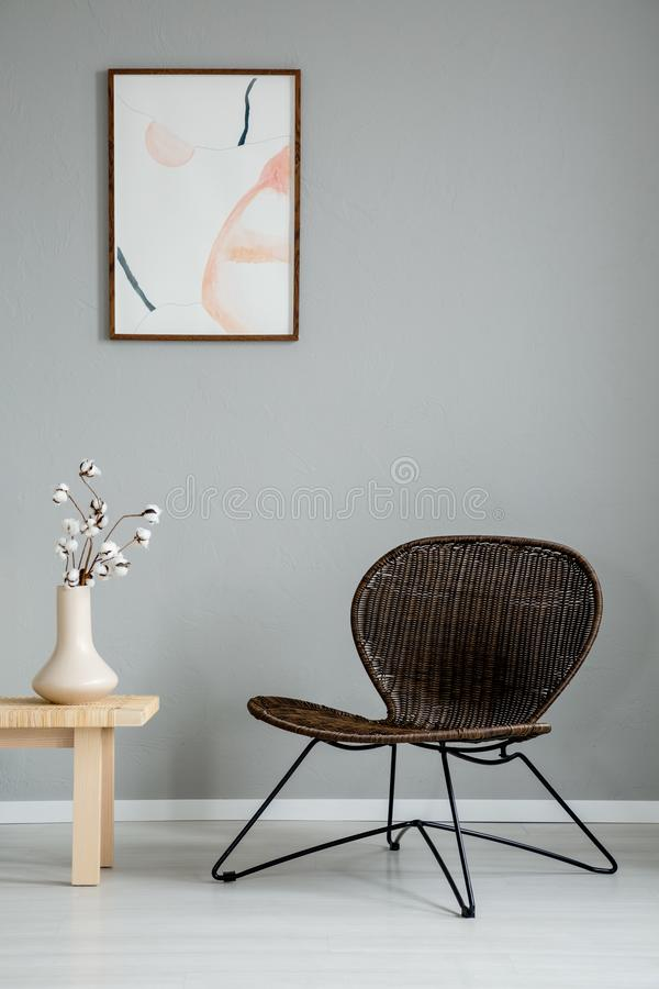 Modern armchair next to wooden table with flowers in grey interior with poster on the wall. royalty free stock image