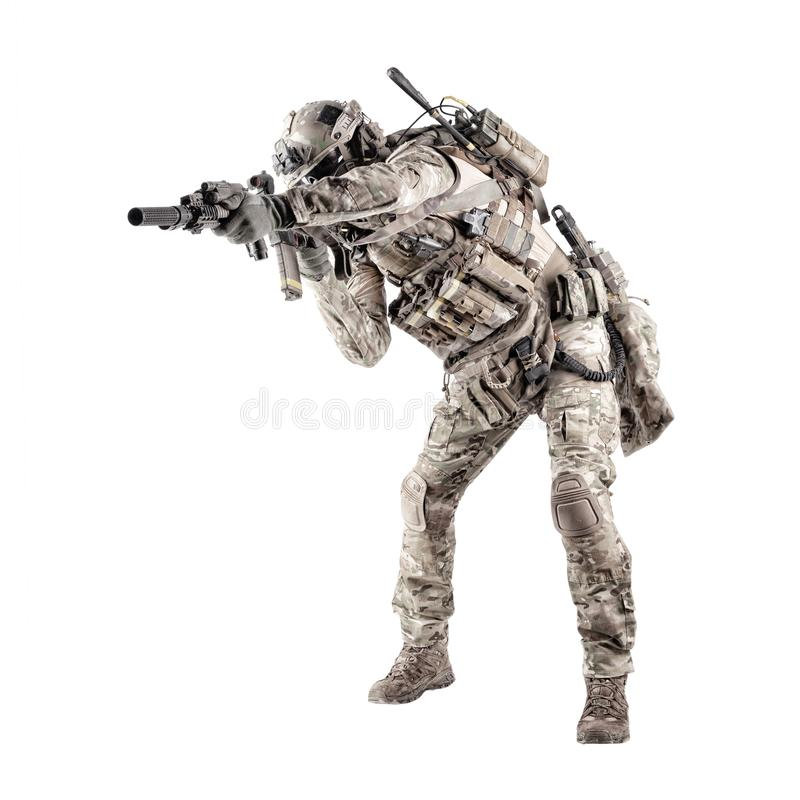 Army soldier crouching with rifle studio shoot. Modern army infantry rifleman in camo uniform, radio headset on helmet, ammo on load carrier, sneaking, crouching royalty free stock photos