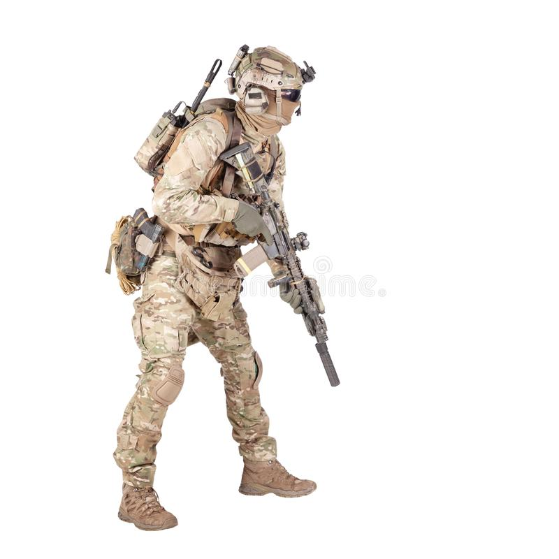 Army soldier crouching with rifle studio shoot. Modern army infantry rifleman in camo uniform, radio headset on helmet, ammo on load carrier, sneaking, crouching royalty free stock images