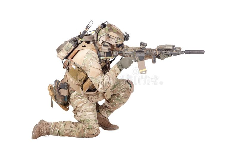 Soldier shooting from knee isolated studio shoot. Modern army infantry soldier in combat uniform and helmet standing on knee, aiming with laser sight on service royalty free stock images