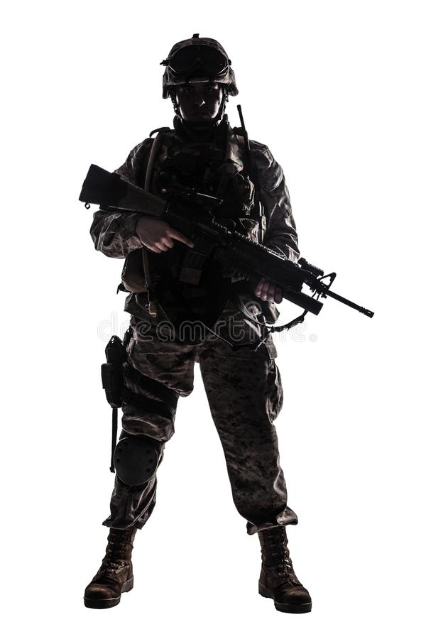 Modern army infantryman low key studio shoot. Full length, low key studio shoot of fully equipped army soldier in camo uniform and helmet, armed with pistol and royalty free stock image