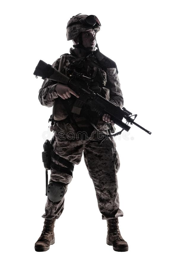 Modern army infantryman low key studio shoot. Full length, low key studio shoot of fully equipped army soldier in camo uniform and helmet, armed with pistol and royalty free stock photography
