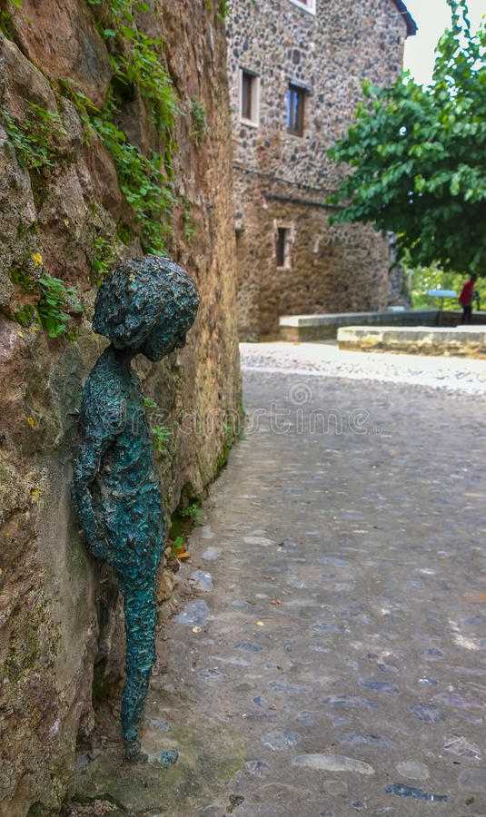 Modern art in a medieval village. In the cobble-stoned ancient streets of the medieval village of Santa Pau in northeastern Catalonia, the modern bronze statue royalty free stock image