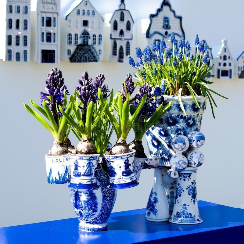 Modern art from old Dutch Delft tiles and pots - Dutch souvenir. Typical dutch blue and white Delft porcelain flower pots, gabled houses and spring flowers royalty free stock photography