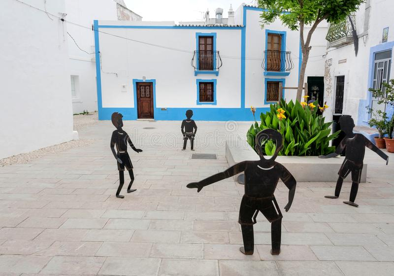 Modern art sculpure with figures of boys playing in courtyard of the old Algarve town stock image