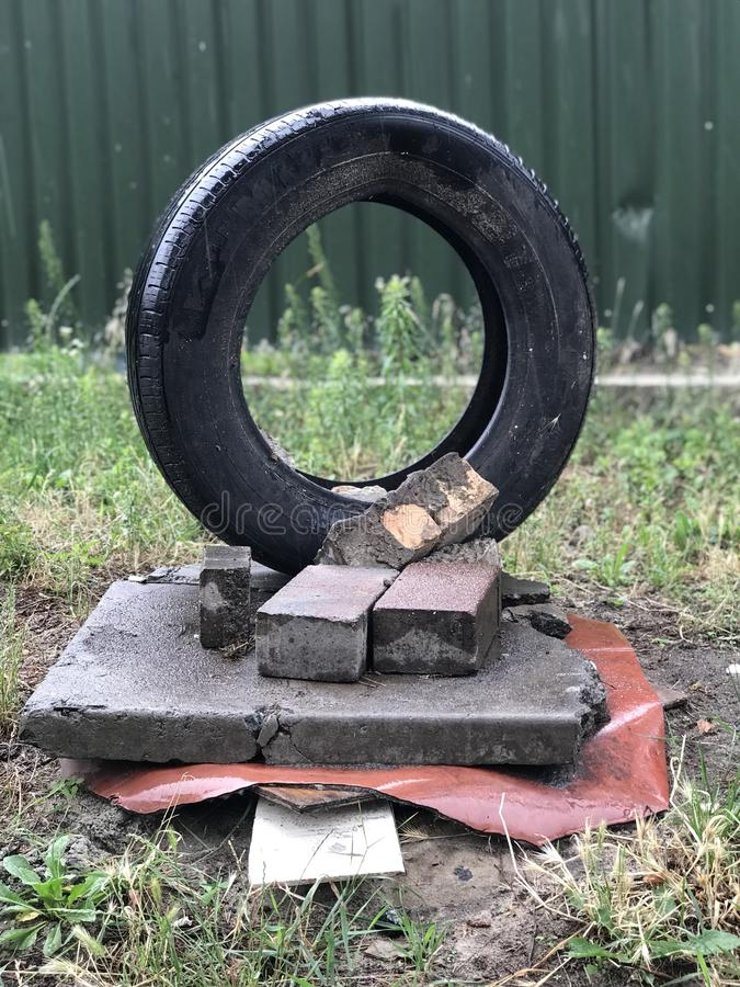 MODERN ART - A tire sits atop concrete slabs and bricks. Modern art includes artistic work produced during the period extending roughly from the 1860s to the royalty free stock photos