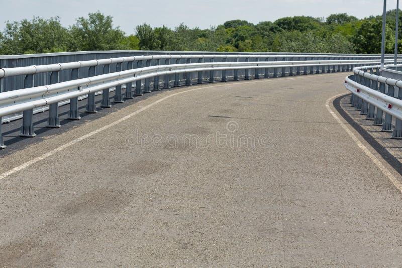 Modern asfaltväg med metallstaket och gångbanacloseupen royaltyfri fotografi