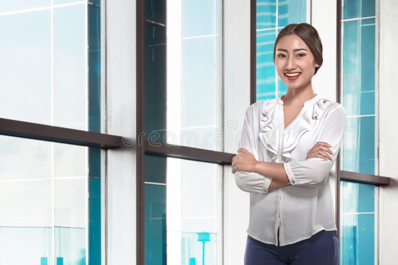 Modern asian business woman with folded arms. Standing in the office royalty free stock photos