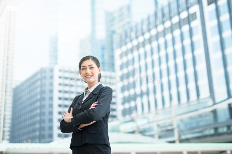 Modern Asian business woman standing outdoors with office building stock photos