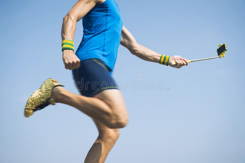 Modern Athlete Running With Smartphone on Selfie Stick royalty free stock photo