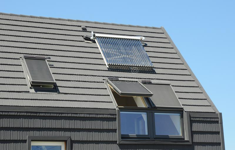 Modern attic roof with solar panels, skylights and blinds window for sun protection and house energy efficiency. Roofing construction stock photo