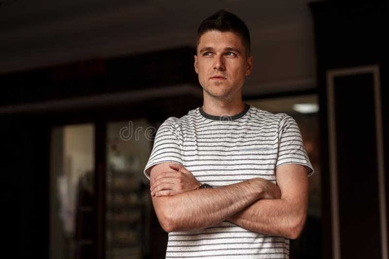 Modern attractive young man in a fashionable striped t-shirt with a stylish hairstyle posing in a dark studio. Urban european guy. Indoors. Trendy menswear royalty free stock photo