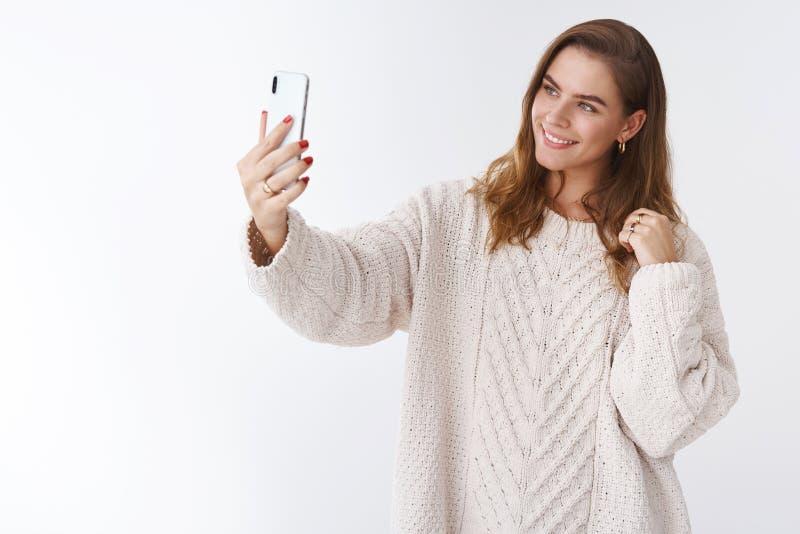 Modern attraktiv kvinna för studioskottglamour som bär den stilfulla lösa hemtrevliga tröjan för att fördjupa vippning för smartp royaltyfri bild