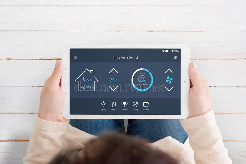 Modern, automated home control app with artificial intelligence on tablet display in woman hands. Top view. Wooden floor in background royalty free stock photos