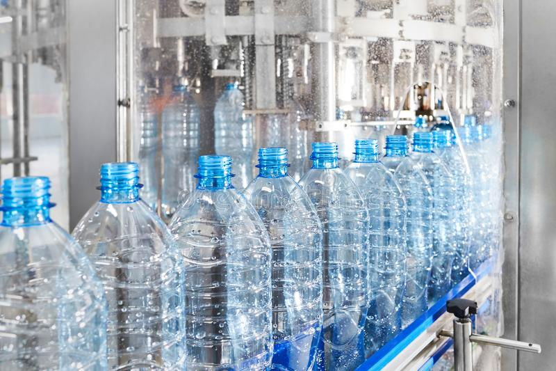 Modern automated production line for water or beverages. Closeup on empty mineral water bottles in raw materials and lines royalty free stock images