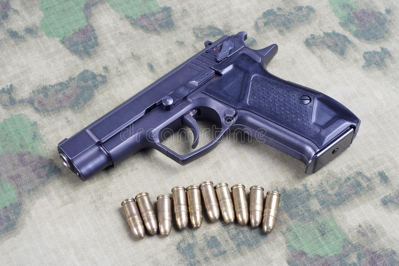 modern automatisch pistool op camouflage stock afbeeldingen